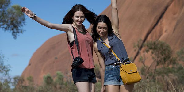 two girls standing in front of uluru