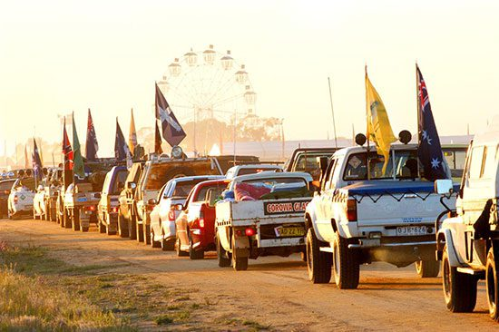 vehicles driving towards a festival